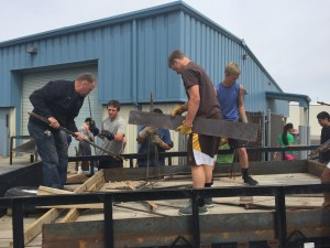Welding teacher, Coach Cody Neville  help his students unload Nevada Copper's donation of scrap metal.